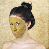 Green cosmetic mask on girl face — Stock Photo