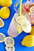 Ice cold lemonade in a glass with pithcer — Stock Photo