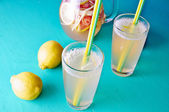 Cold summer dring - lemonade in pitcher with lemons around it — Stockfoto