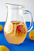 Fresh ginger lemonade with strawberry in pithcer — Stock Photo