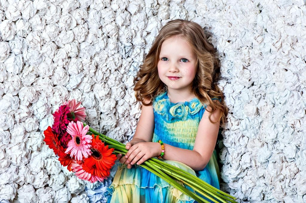 Fashion baby face beautiful child with fair hair in a pink dress holds flowers — Stock Photo #13217270
