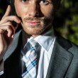 Men in suit speaks by phone babbling down — Stock Photo #13267253