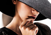 Girl in black hat touching face and lips — Stockfoto
