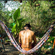 Man with tattoos sitting on a hammock — Stockfoto