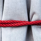 Fabric texture with a rope — Stock Photo