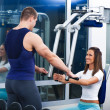 Stock Photo: Young beautiful girl exercise with personal trainer