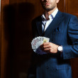 Man in a suit player sits with cards in a hand — Stock Photo