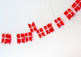 The small Danish flags garland on white cracked wall — Stock Photo