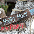 Happy hour, body paint board notices on tree trunk — Stock Photo