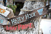 Happy hour, body paint board notices on tree trunk — ストック写真