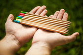Hands holding colored pencils — Stock Photo