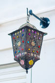 Traditional color lamp hanging from a stucco wall — Stock Photo