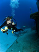Underwater Photographer looking at a Sunken Ship — Stock Photo