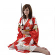 French young girl geisha in red silk kimono with japanese sword — Stock Photo #25892751