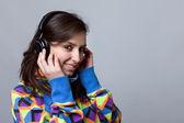 Sorridente giovane donna ascoltando musica su sfondo grigio — Foto Stock