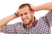 Jovem casual com uma dor de cabeça em um fundo branco — Fotografia Stock