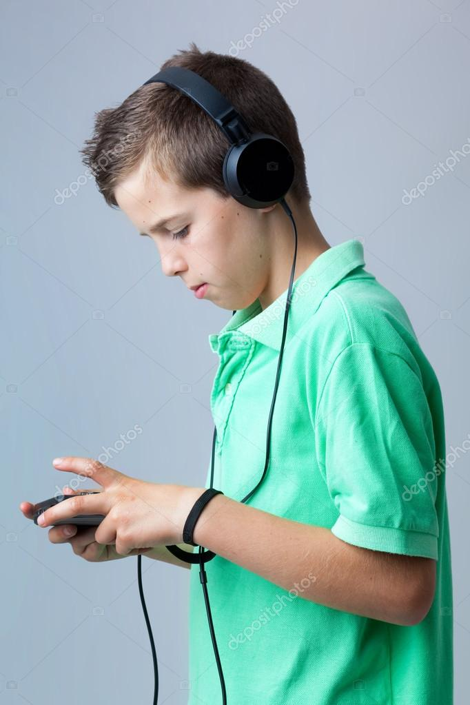 Boy playing game console against grey background  Stock Photo #12929551