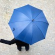 Business man hidden under umbrella and checking if it's raining — Stock Photo