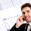 Young smiling businessman calling on phone at office — Stock Photo