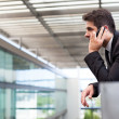 Постер, плакат: Young business man talking on cell phone at modern office