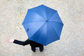 Business man hidden under umbrella and checking if it's raining — Foto Stock