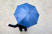 Business man hidden under umbrella and checking if it's raining — Stock Photo