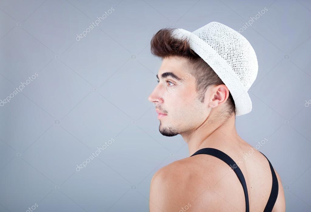 Portrait of a handsome young man in hat against grey background   Stock Photo #12931641