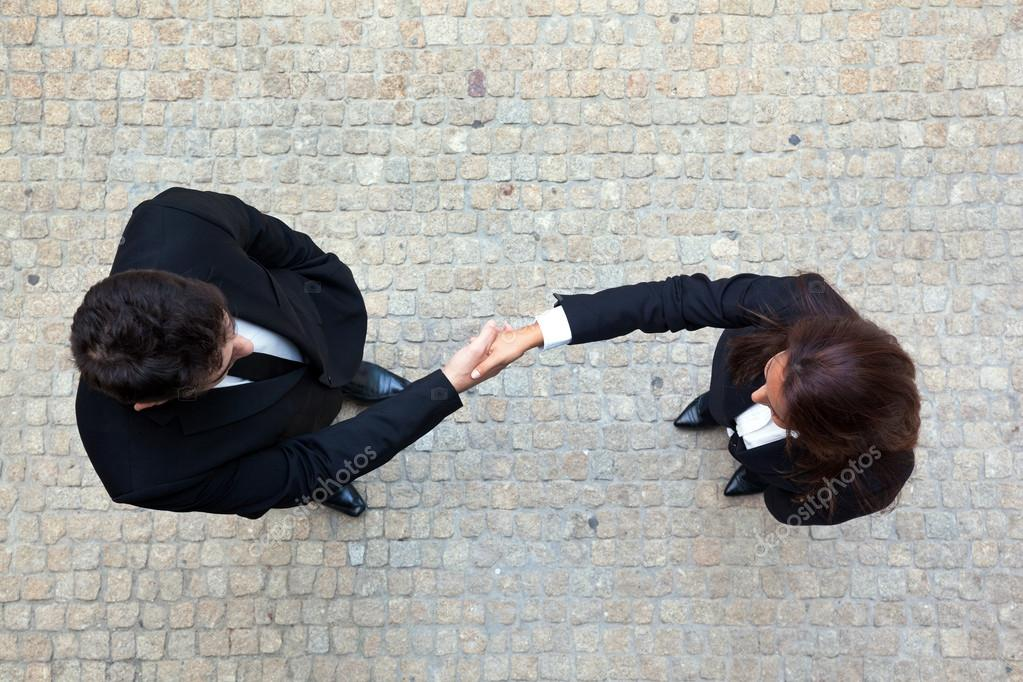 Business handshake between businessman and businesswoman — Stock Photo #12933628