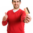 Happy smiling young man holding a credit card and gives thumb up — Stock Photo
