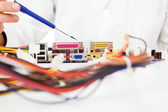 Computer Engineer examining,repairing a electronic circuit, isolated over white background — Stock Photo