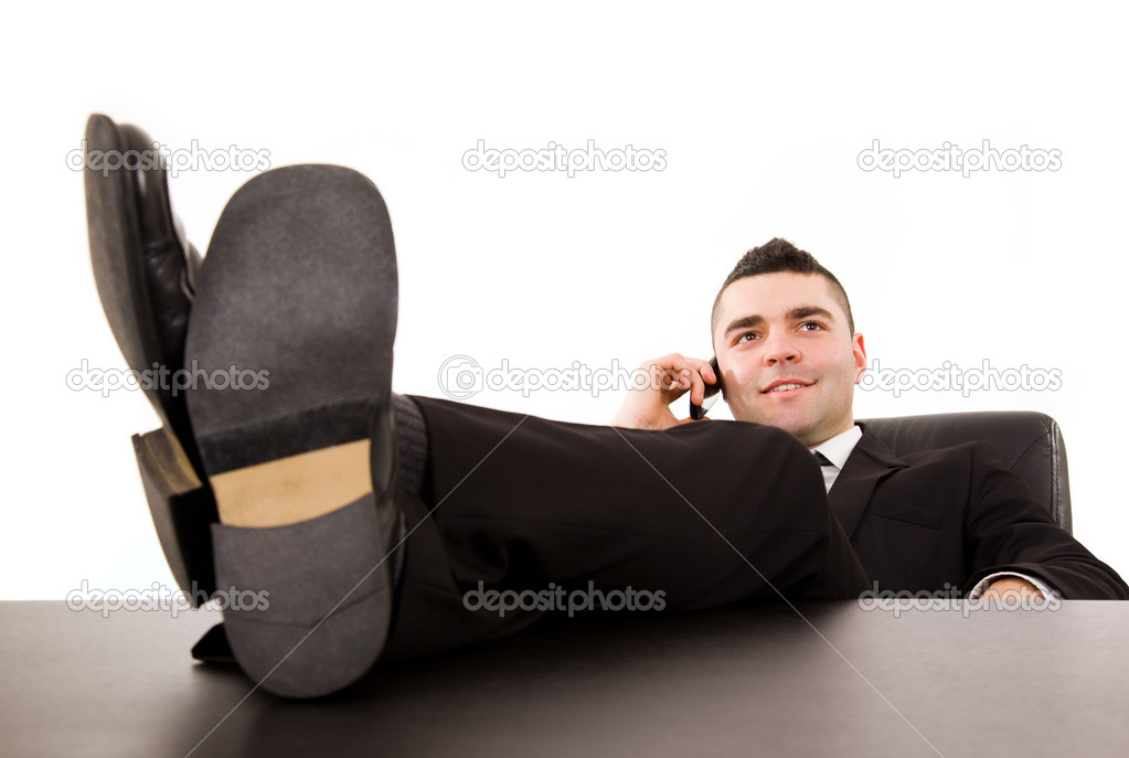 Young business man relaxing at office desk and talking on mobile phone, isolated on white — Stockfoto #12947105