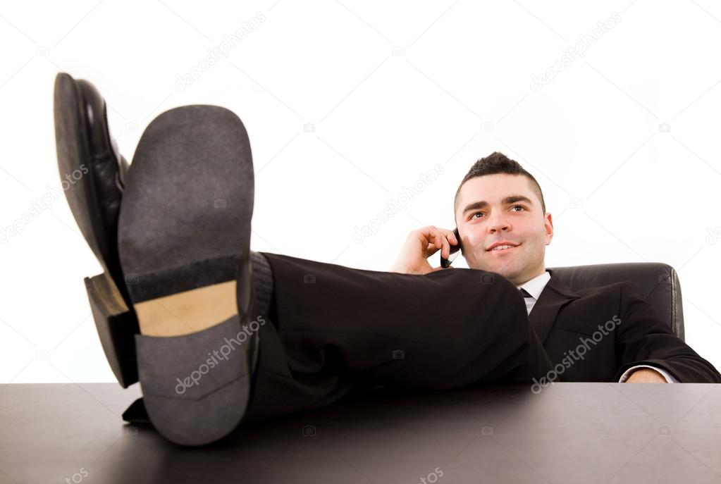 Young business man relaxing at office desk and talking on mobile phone, isolated on white — Photo #12947105