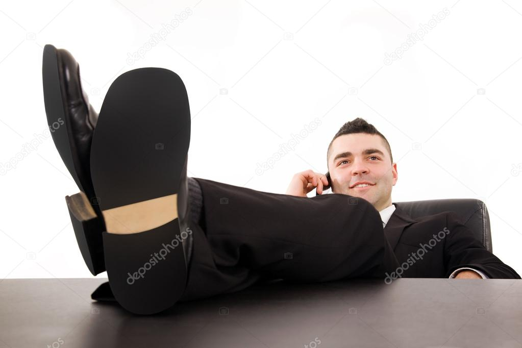Smiling young business man relaxing at office desk and talking on mobile phone, isolated on white  — Stock Photo #12947172