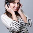 Smiling happy young woman listening to music over gray backgroun - Stock Photo