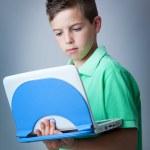 Llittle boy with laptop against grey background — Stock Photo