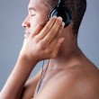 Young black man listening to music with headphones over grey background — Stock Photo