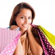 Closeup portrait of beautiful young woman holding shopping bags over white — Stockfoto