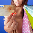 Beautiful shopping woman holding a credit card on blue background - Stock Photo