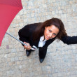 Young business woman checking if it's raining - Stock Photo