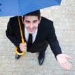 Smiling young business man checking if it's raining — Lizenzfreies Foto