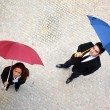 Businessman and businesswoman standing with umbrella outdoors - Stock Photo