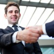 Businessman shaking hands at the office on blurred background — Stock Photo