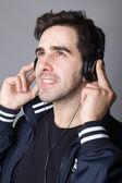 听音乐用耳机一个年轻人的肖像 — 图库照片