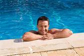 Mokré vydělané mladý muž pózuje v bazénu — Stock fotografie
