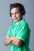 Portrait of a smiling boy listening to music on headphones over — Stock Photo