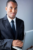 Smiling African American young businessman with laptop — Stock Photo