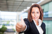 Smiling young businesswoman giving thumbs up — Stock Photo