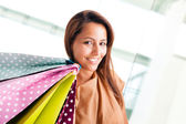 Beautiful young woman holding bags and smiling at the shopping — Stock Photo