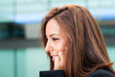 Closeup of young business woman talking on cell phone at the office — Stock Photo