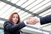 Businesswoman shaking hands at the office on blurred background — Stock Photo